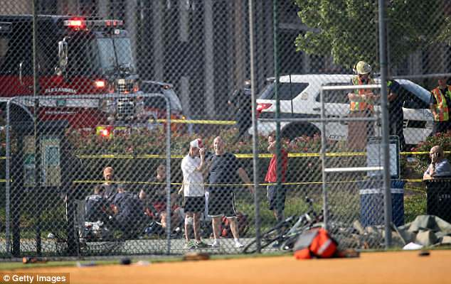 Investigators and men dressed in baseball gear gather at Eugene Simpson Field, the site where a gunman opened fire on the Republican practice session.