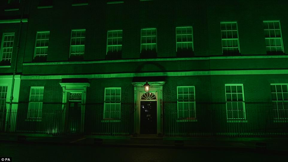 Thirteen sites across London including Downing Street (pictured) and Kensington Palace glowed green - the adopted colour of the Grenfell community - in a show of solidarity across capital's skyline