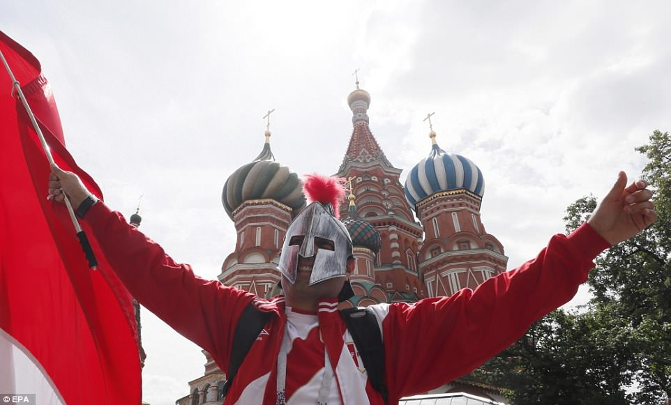 A Peruvian fan in a mask and proudly showing off his nation's colours poses for a photograph in front of the landmark