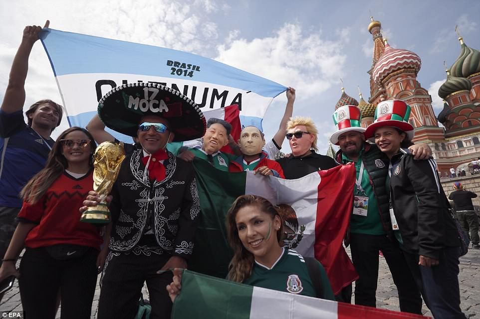 Mexican fans, including some wearing masks of Vladimir Putin, Donald Trump and Kim Jong-un, pose for a photograph