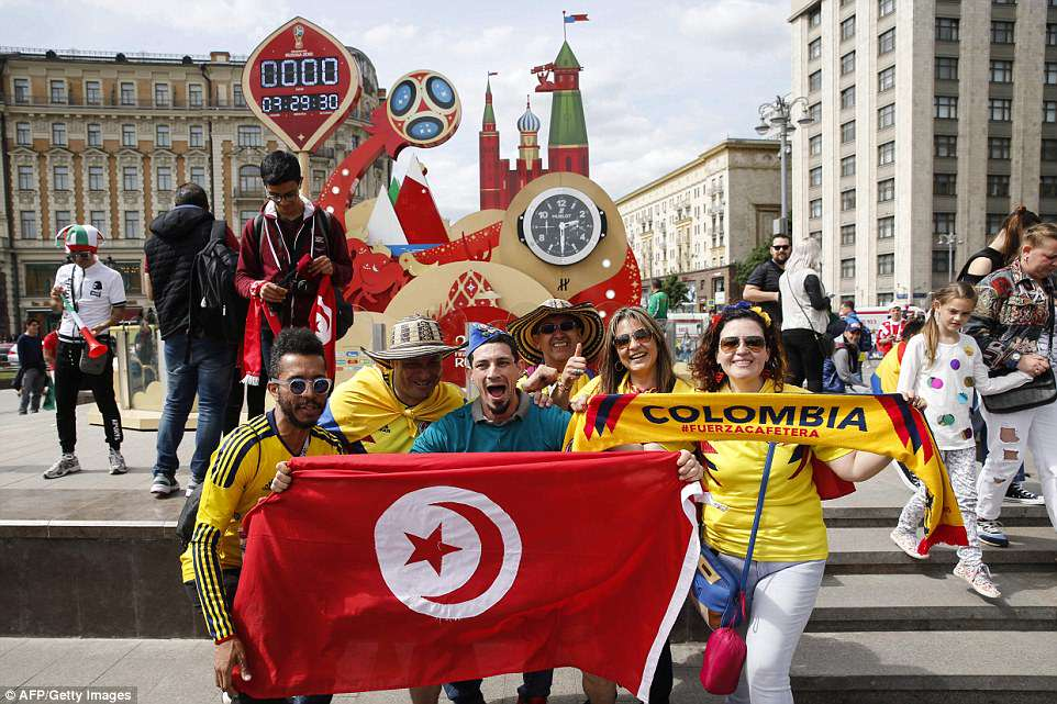 Supporters of Tunisia and Colombia combine for a photograph in front of a clock counting down to kick-off in Moscow