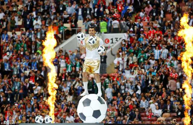 An entertainer balances on top of an inflatable football and juggles a further three as fire blazes behind him