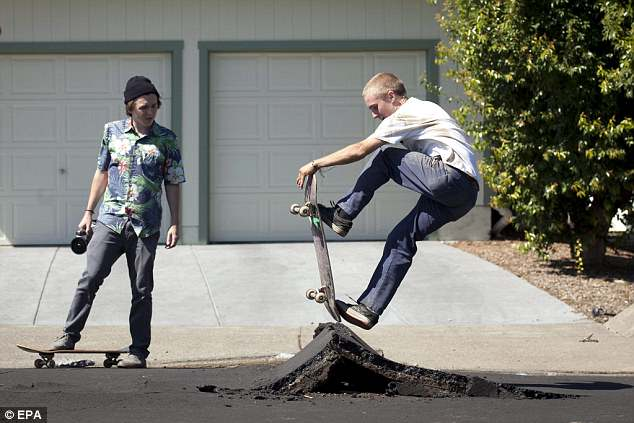 Skater Gabe Haugen (R) of Napa took advantage of a buckled street after a 6.1 magnitude earthquake hit the San Francisco Bay Area, in Napa, California, USA, 24 August 2014.   More than 70 people were sent to hospital with injuries and power outages darkened multiple cities in northern California after a 6.1-magnitude earthquake struck early on 24 August. The United States Geological Survey (USGS) said the earthquake struck at 3:20 am (1020 GMT) at a depth of 10.8 kilometres. It was located nine kilometres south-west of the Napa wine region, and 81 kilometres north of San Francisco.