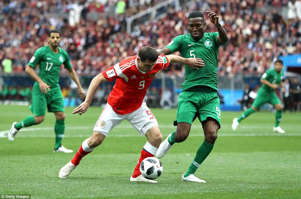 Alan Dzagoev (left) fends off a challenge fromOmar Hawsawi as the hosts go in search of the opening goal