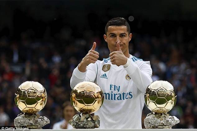 Cristiano Ronaldo shows off three of his five Ballon d'Or trophies, the same number as Messi