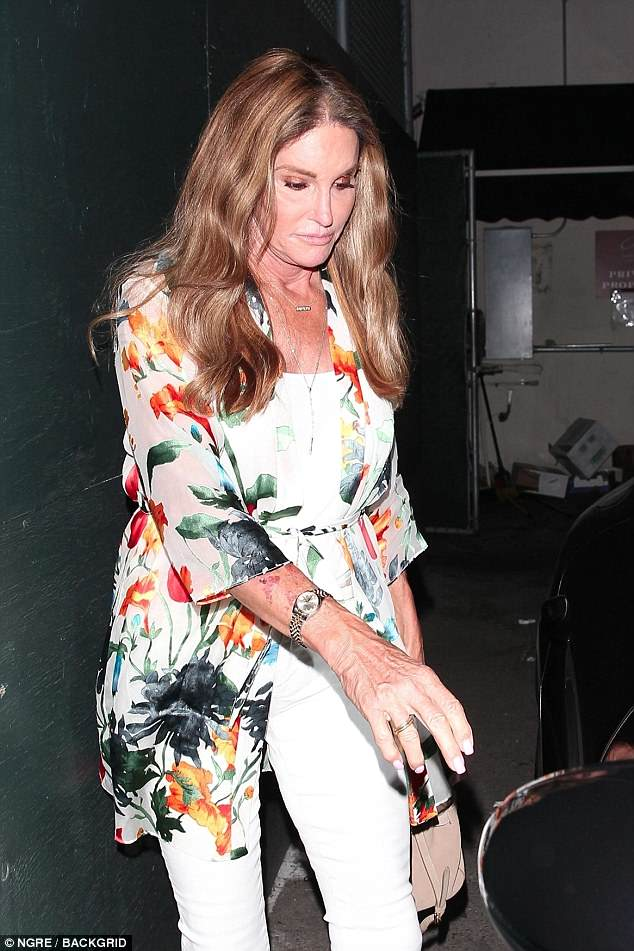 Nice: Caitlyn kept covered up for the night out wearing a vibrant floral kimono which featured long sleeves and a thigh-skimming hem