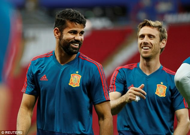 Striker Diego Costa (left) shares a joke with Arsenal defender Nacho Monreal during training