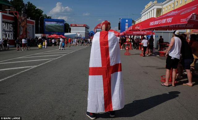 An England fan with the St George's Cross patterned into his hair carries a flag in Nizhny Novgorod today