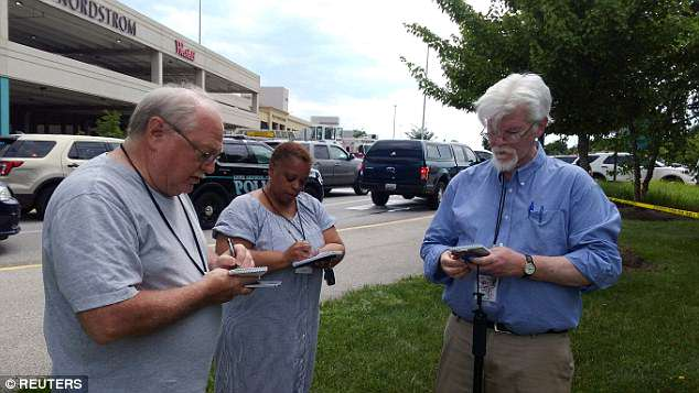 Gazette journalist E.B Furgurson (R) takes notes with two other people as police officers respond to an active shooter inside his newsroom