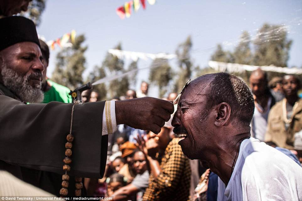 'God's work': A man is seen crying hysterically as priest and healerMemehir Girma Wedimu touches him with a cross