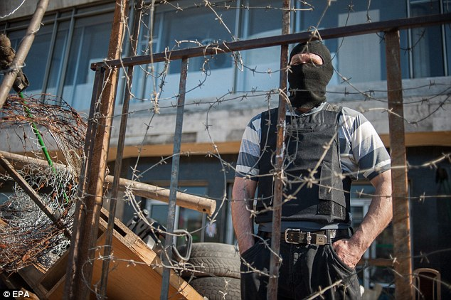 A masked pro-Russian protestor stands behind a barb wire crowned barricade near the occupied regional administration building in Donetsk, Ukraine, in 2014