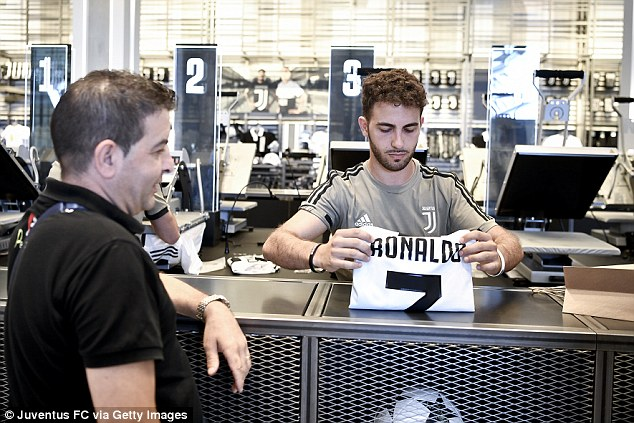 A staff member at Juventus' club store prints a Cristiano Ronaldo shirt for a happy customer