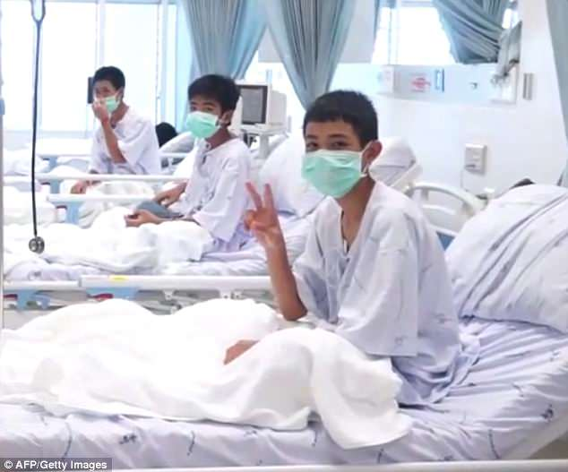 Members of the Wild Boars football team are seen being treated at a hospital in Chiang Rai, their parents on the other side of a glass window