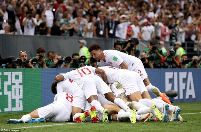 Defender Kyle Walker jumps up on top of his England team-mates as they pile on the goalscorer, Kieran Trippier