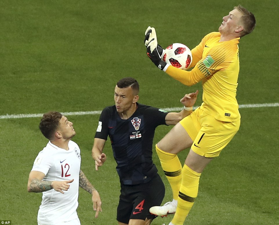 England goalkeeper Pickford leaps high and catches the ball in his gloves ahead of the efforts of Croatia forward Perisic