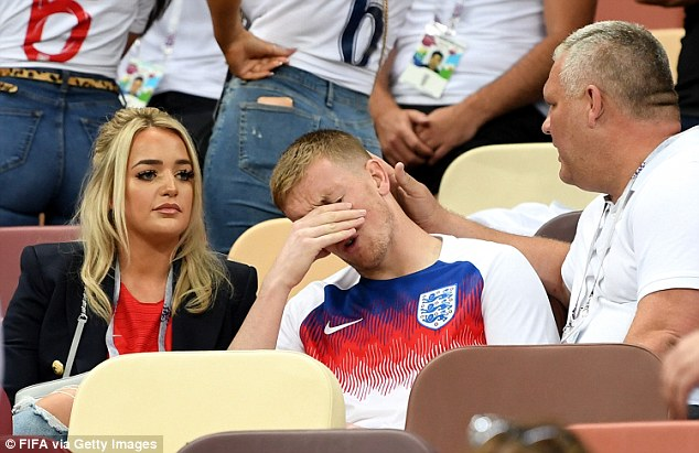 Jordan Pickford of England looks dejected with Megan Davison after the 2018 FIFA World Cup Russia Semi Final match between England and Croatia