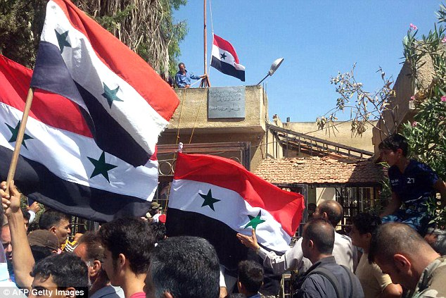 Syrian men waving their national flag, above, near the city council, after the raising of the government¿s flag in the rebel-held city of Daraa