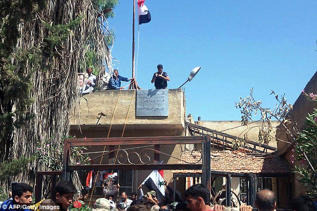 A handout picture released by the official Syrian Arab News Agency (SANA) today shows Syrian men also waving the national flag near the city council