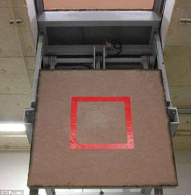 The trap door marked with a red square where an inmate stands, is seen opened at the execution chamber