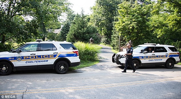 Photos show several police cruisers pulled up on the street outside his home on Thursday