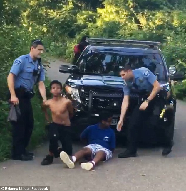The incident unfolded at Minnehaha Regional Park, two of the four pictured above being taken into the cop car by the officers before they were later released