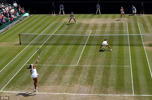 Heather Watson (serving) and Tatjana Maria during the doubles on day nine of the Wimbledon Championships