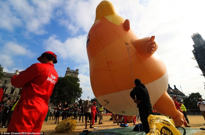 The Trump Big Baby inflatable Blimp is installed in Parliament Square as hundreds of people look on