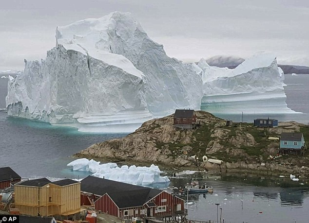 Too close for comfort, the iceberg, which towers over the village of Innarsuit, northwestern Greenland, could suddenly lose a chunk of ice and cause a flood of water