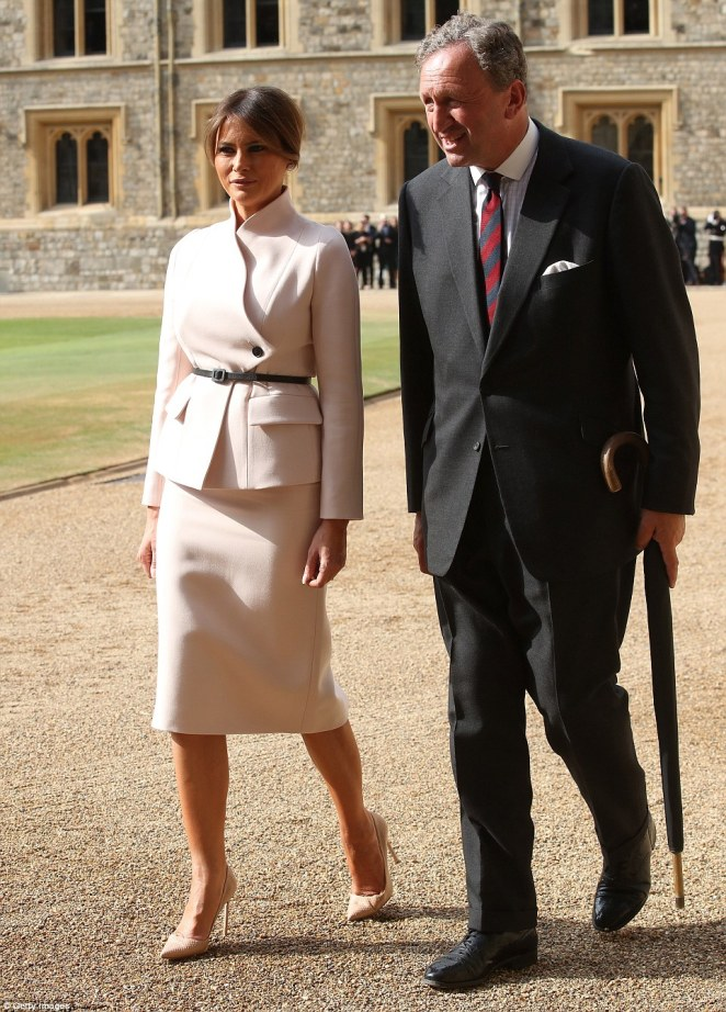 New friend: Melania had her own escort to chat to as the group made their way around the Quadrangle of the castle