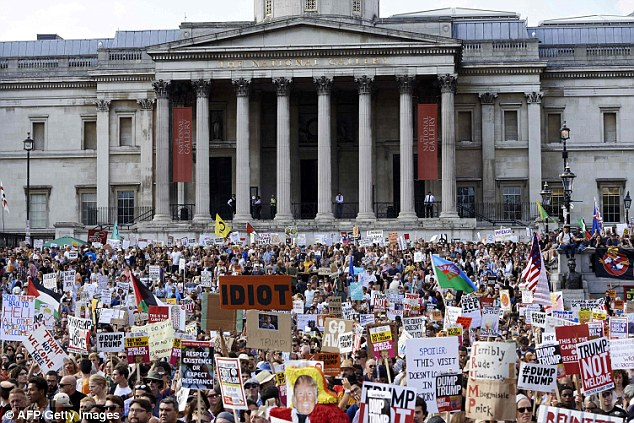Thousands of protesters brandish placards in front of the National Gallery in Trafalgar Square