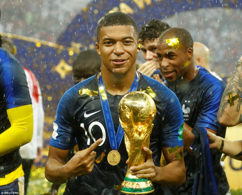 Mbappe, 19, holds the shining World Cup trophy as he celebrates becoming one of the youngest winners in its long history