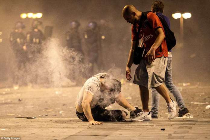 French fans faced off against riot police on the packed Champs-Elysee as officers attempt to disperse massive crowds. Pictured:A man falls to the floor after inhaling tear gas as French football fans clash with police following celebrations around the Arc de Triomph
