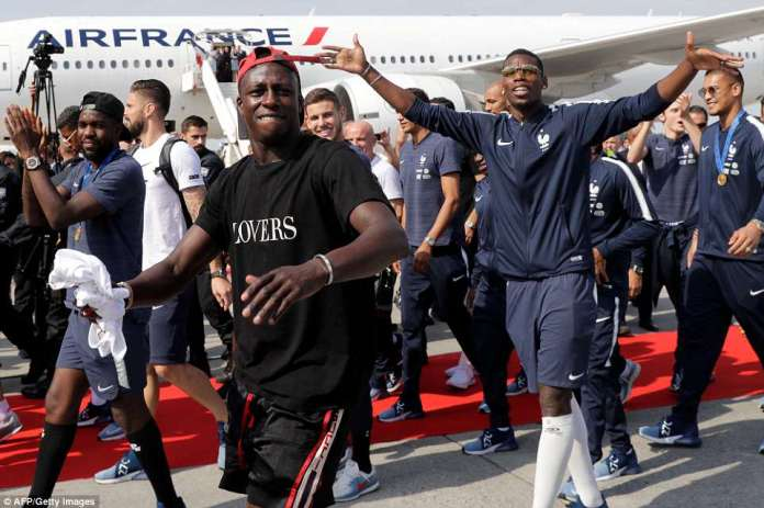 France's defender Samuel Umtiti, defender Benjamin Mendy and midfielder Paul Pogba celebrate after disembarking from their plane upon their arrival at the Roissy-Charles de Gaulle airport