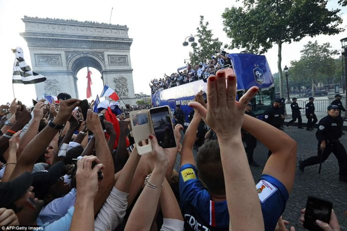 Fans were seen cheering and taking photos of the team as they made their way down the street near the Arc de Triomphe