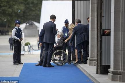 Mr Juncker was also photographed unable to climb the steps to the podium and being pushed around in a wheelchair at last week's NATO summit (pictured) - raising questions about his health and ability to govern