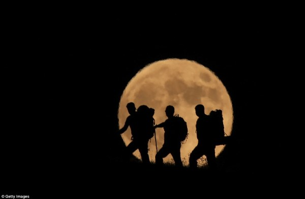 Three men in the moon: Walkers are pictured hiking up Mount Artos in Turkey as the Blood Moon dazzles behind them