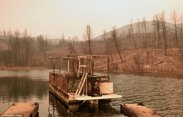 A partially burned boat floats on Whiskeytown Lake during the Carr fire near Whiskeytown, California, on Friday, near where to more than 100 homes were burned