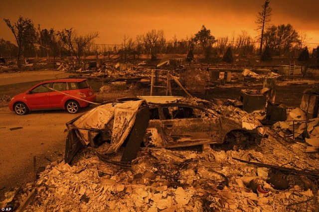 Two vehicles that endured the Carr Fire, one with minor cosmetic damage and one destroyed, rest among leveled homes in the Lake Keswick Estates area of Redding on Friday evening