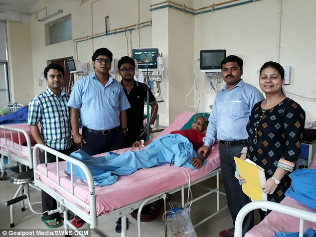 Arati Adhikary (pictured recovering in a hospital bed) went to hospital in severe pain and with a bloated stomach difficulty breathing, where doctors realised she had ovarian tumours taking up 80 per cent of her abdomen
