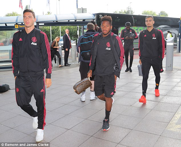 New signing Fred (centre) walks into Manchester airport with Matteo Darmian (left) on Sunday