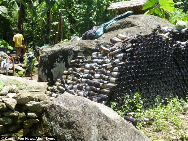 A giant pile of beer bottles stacked up against a rock on the road to theBarun Valley