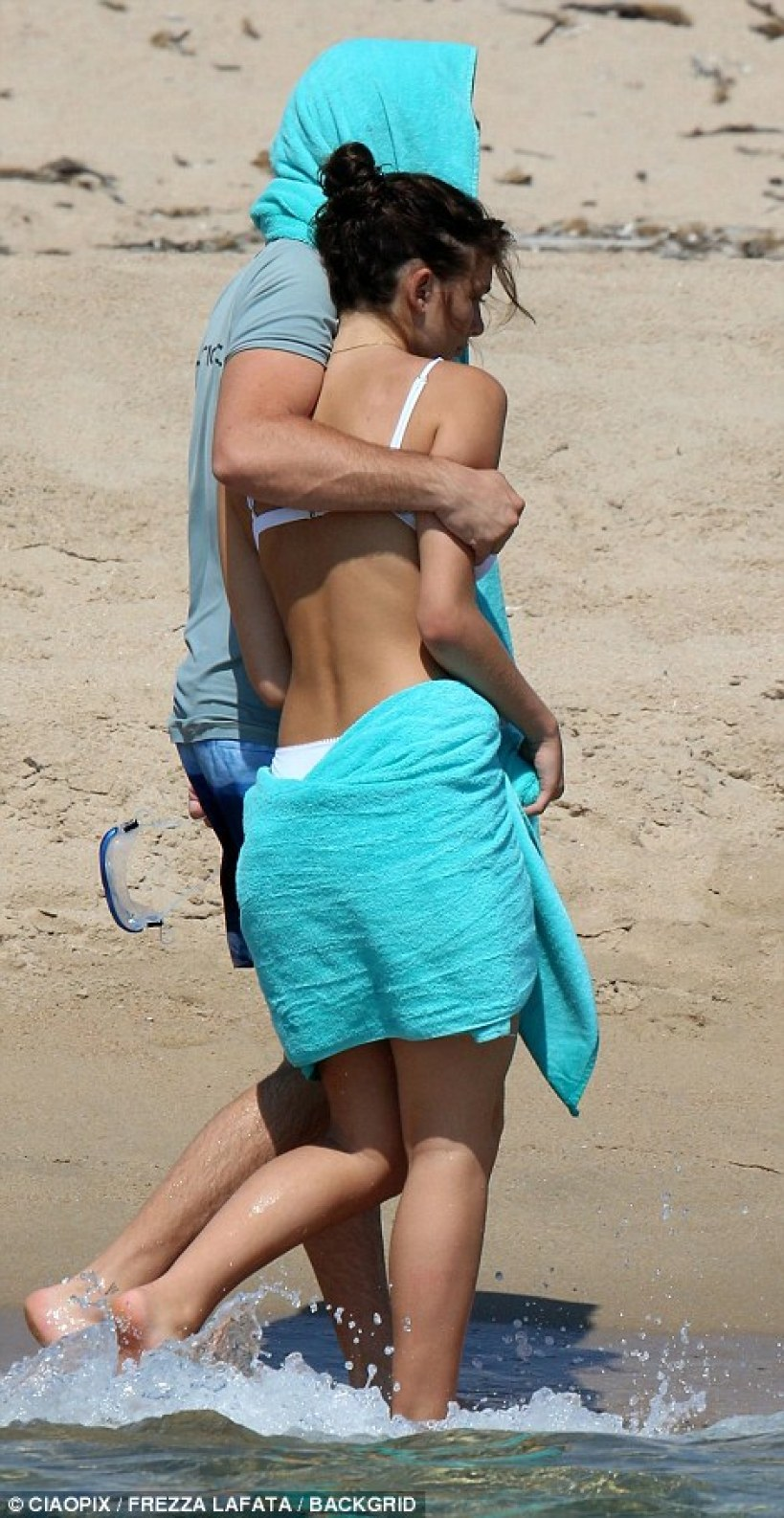 Packing on the PDA: Leonardo wrapped a loving arm around his new girlfriend's shoulders as they strolled along the shoreline