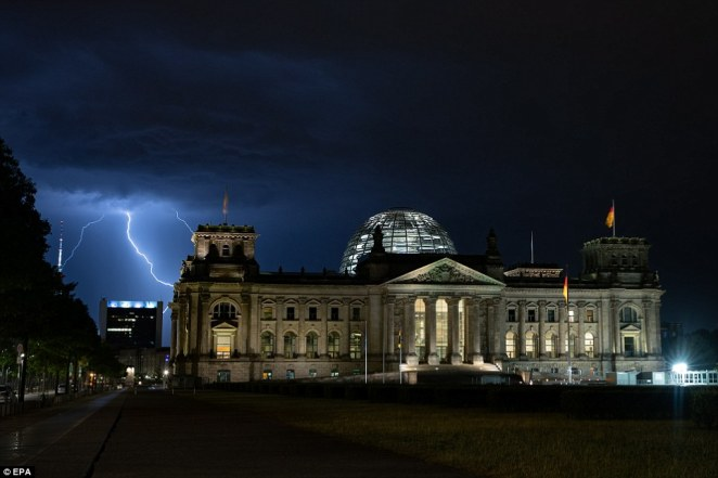Storms have also hit in Germany where lightning is seen behind the Reichstag building in Berlin on Thursday night