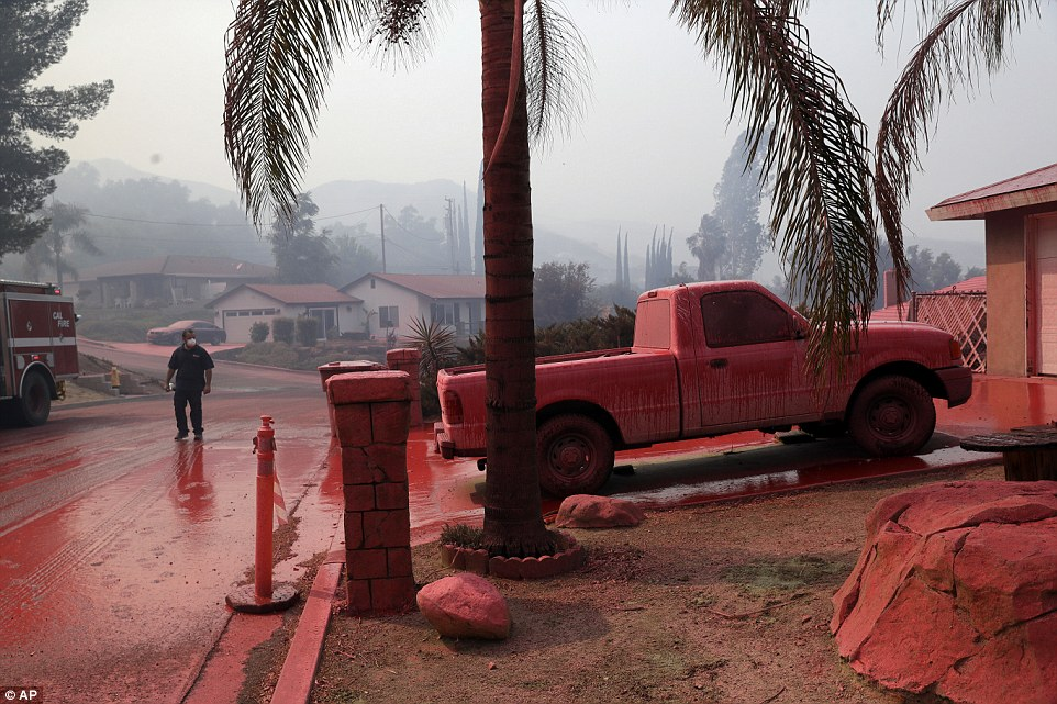 A truck and a street are covered in fire retardant dropped by an air tanker as crews battle a wildfire on Friday in Lake Elsinore