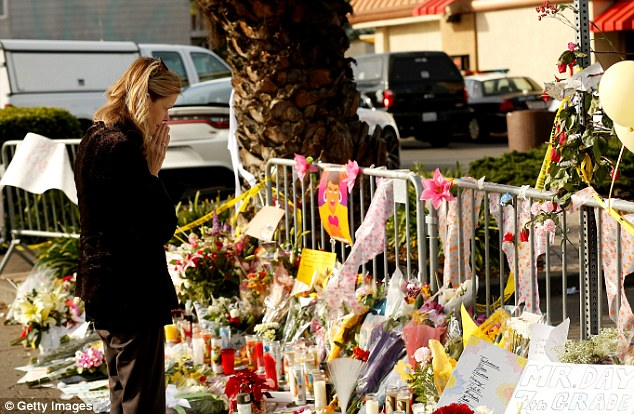 A woman pays tribute to the people who lost their lives during a fire at the Oakland warehouse