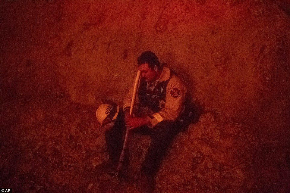 In northern California, a firefighter battling the Mendocino Complex is seen taking a rest on Tuesday