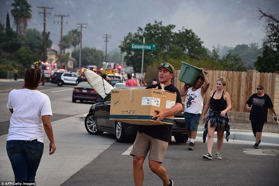 Residents flee a neighborhood with their belongings after a spot fire broke out at the Holy Fire in Lake Elsinore, California