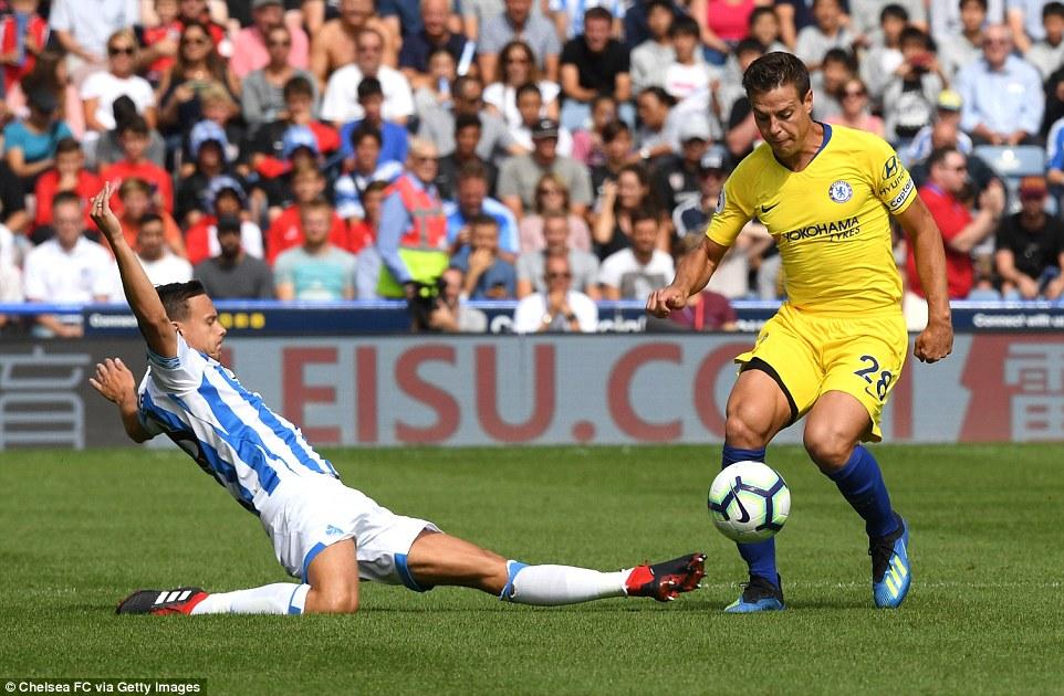 Huddersfield midfielder Jonathan Hogg (left) mistimes his sliding challenge asCesar Azpilicueta skips past him with ease