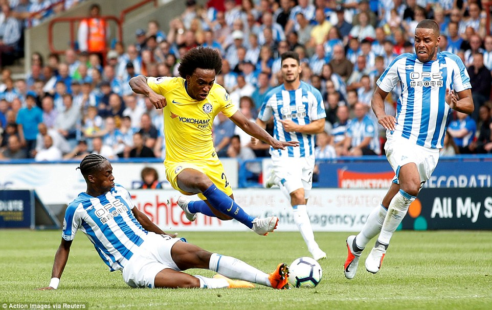 Willian is halted in his tracks as Huddersfield's Kongolo comes across and slides in to intercept the Chelsea forward