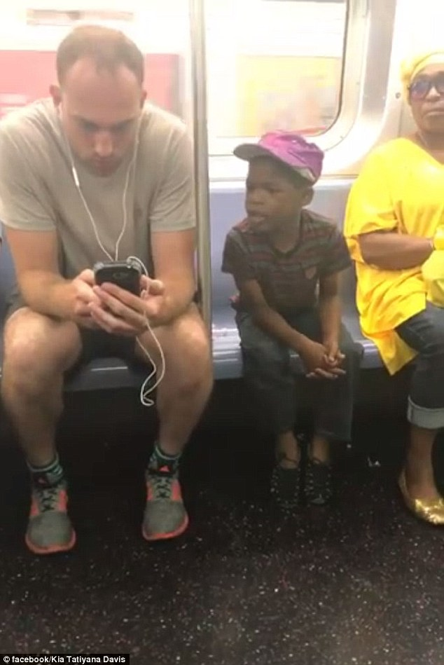 The clip shows an adorable young boy enamored by the phone being held by the much larger adult sitting next to him